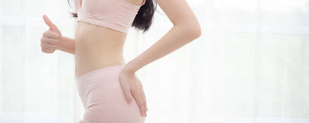 Closeup asian woman wear underwear beautiful body belly slim shape sexy with diet at room, girl thin wear bra gesture thumbs up with weight loss, health and lifestyle concept, banner website.