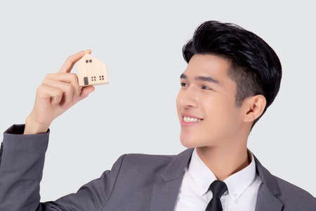 Young asian business man holding the home symbol of saving for future, insurance agent and credit, ownership house, debt and loan of finance, purchase home and refinance, investment real property. Stock Photo