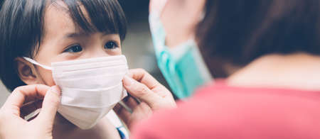 Mother take care daughter with face mask for protection disease flu or covid-19 outdoors, mom wearing on medical mask with child safety for protect outbreak of pandemic, banner website. Stock Photo