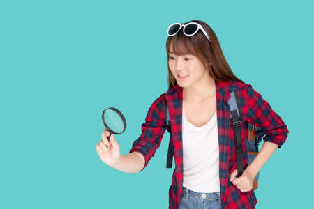 Beautiful portrait young asian woman looking something with magnify glass for planning guide to travel summer trip, asia girl search route and location for destination of journey in vacation. Stock fotó
