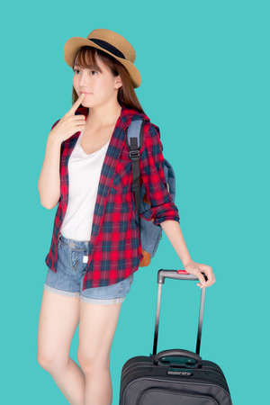 Beautiful young asian woman pulling suitcase isolated on blue background, asia girl having expression is cheerful holding luggage walking in vacation with excited, journey and travel concept.
