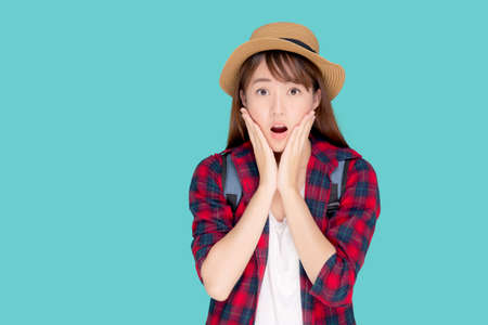 Beautiful portrait young asian woman smiling and surprise wearing travel summer fashion tourist in vacation isolated on blue background, girl shocked expression and emotion, holiday concept. Stock fotó
