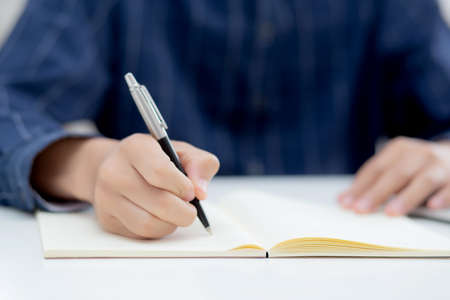 Closeup hand of man writing on notebook with pen on desk, freelance is author, businessman write on notepad on table, book, letter and report, finance and document, business or education concept.