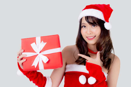 Beautiful portrait young asian woman happy holding red gift box with excited in xmas holiday isolated on white background, asia girl surprise and celebrating in festive Christmas and new year. Stock Photo