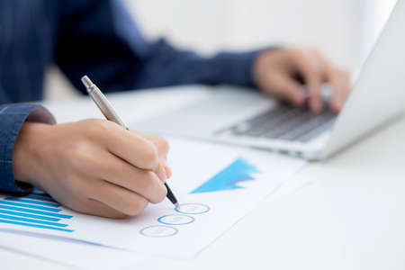 Hand of business man pointing document data graph and chart with pen, marketing and investment, report of statistics profit for financial, economic and growth of finance, management and planning.