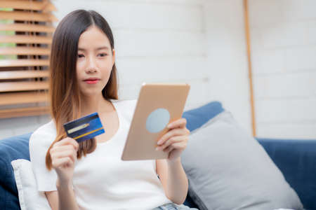Young asian woman smiling holding credit card shopping online with tablet computer buying and payment, girl using debit card purchase or transaction of finance, lifestyle and e-commerce concept. Фото со стока