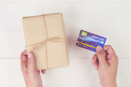 Hand of man holding credit card and online shopping for giving gift box with kraft paper on wooden background, present for celebration on desk in Christmas day or holiday, top view, flat lay.