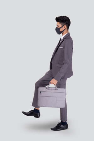 Portrait young asian businessman in suit wearing face mask walk step for protective covid-19 isolated on white background, business man and healthcare, quarantine for pandemic coronavirus, new normal.