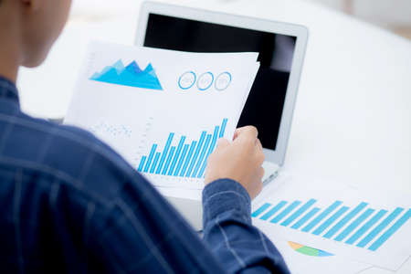 Hand of young business man looking document data graph and chart paper, marketing and investment, report of statistics profit for financial, economic and growth of finance, management and planning.