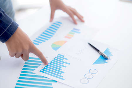Hand of young business man pointing document data graph and chart paper, marketing and investment, report of statistics profit for financial, economic and growth of finance, management and planning. Stok Fotoğraf