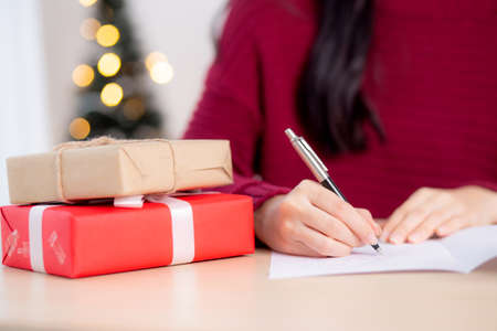 Closeup hand of young asian woman writing postcard in Christmas day at home, eve and celebrate, female writing message on greeting card with giving gift box in holiday, congratulation and celebration.
