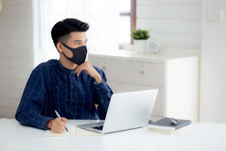 Young business man in face mask planning and working from home on laptop computer on desk for protection for outbreak of covid-19, male quarantine stay home using notebook on desk, new normal.