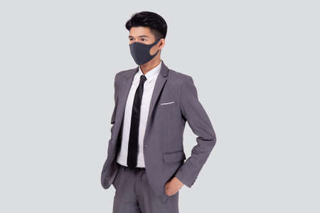 Portrait young asian businessman in suit wearing face mask for protective covid-19 isolated on white background, business man and healthcare, quarantine for pandemic coronavirus, new normal.