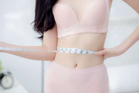Beautiful young asian woman sexy body slim measuring abdomen for control weight loss in the room, beauty girl belly thin have cellulite with tape measure for diet, health and wellness concept.