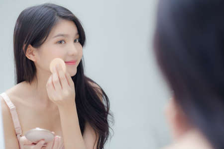 Closeup hand of young asian woman holding product cosmetic applying cream in jar, beautiful girl hand touch lotion for rejuvenation, beauty perfect, treatment and skin care and health concept.