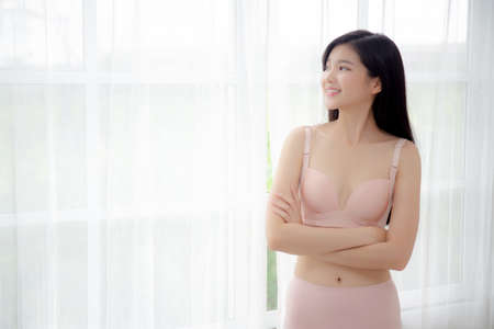 Beautiful portrait young asian woman sexy standing the window and smile while wake up with health, body of girl happy with freshness and cheerful with wellbeing, lifestyle and relax concept.