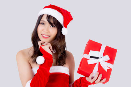 Beautiful portrait young asian woman excited holding red gift box have card or tag in xmas holiday isolated on white background, asia girl surprise and celebrating in festive Christmas and new year.