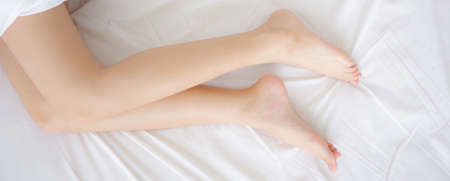Beautiful leg of woman slim sexy on bed at bedroom, skin smooth of beauty girl feet health care, comfort and wellbeing, female lying sleep for relax with blanket, lifestyle concept, banner website.