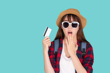 Beautiful young asian woman wear hat and sunglasses with showing and surprise with credit card to travel summer trip isolated on blue background, girl journey in vacation with payment finance on card. Stok Fotoğraf