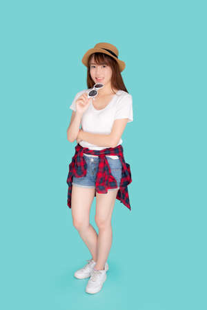 Beautiful portrait young asian woman wear hat and holding sunglasses smiling confident enjoy journey summer trip in vacation isolated on blue background, tourist asia girl cheerful with travel. Stok Fotoğraf