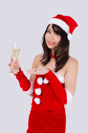 Beautiful portrait young asian woman in Santa holding glass of champagne with party celebrating in xmas holiday isolated on white background, asia girl drink beverage, Christmas and new year concept.