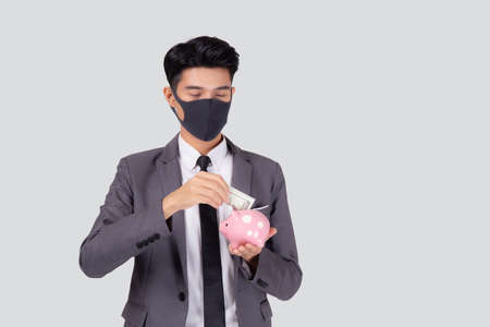 Young asian businessman in face mask holding money dollar and piggy bank isolated on white background, crisis of economic, business man in mask investment finance and saving during disease covid-19.