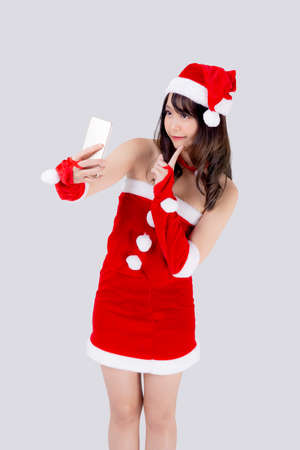 Beautiful portrait young asian woman in Santa cheerful taking a photo in Christmas holiday isolated on white background, asia girl selfie with phone celebrating in xmas with smiling and happy.