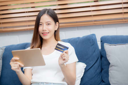 Young asian woman smiling holding credit card shopping online with tablet computer buying and payment, girl using debit card purchase or transaction of finance, lifestyle and e-commerce concept. Stok Fotoğraf