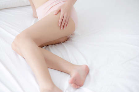 Beautiful young asian woman touch skin leg smooth with cream and lotion for hydration and smooth, girl applying body care and cosmetic for silky and soft, beauty perfect with wellness, health and care.