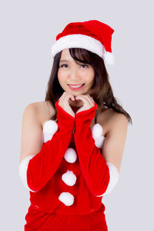 Beautiful portrait young asian woman Santa costume wear hat smiling gesture heart with hand in holiday xmas, beauty model asia girl cheerful celebrating in Christmas isolated on white background.