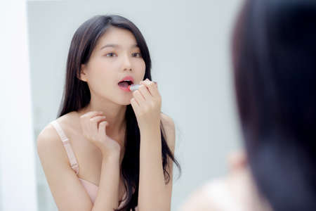 Beautiful young asian woman applying lipstick pink with style bright and shiny on mouth, beauty girl looking mirror for makeup cosmetic with lip elegance, fashion make up with luxury and sexy.