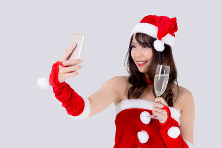 Beautiful portrait young asian woman in Santa holding glass of champagne and selfie with phone in party celebrating in xmas holiday isolated on white background, Christmas and new year concept. Stok Fotoğraf
