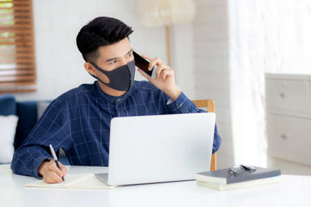 Young asian business man in face mask talking smartphone and work on laptop computer for protect covid-19, businessman quarantine work from home and writing notebook, social distancing and stay home.