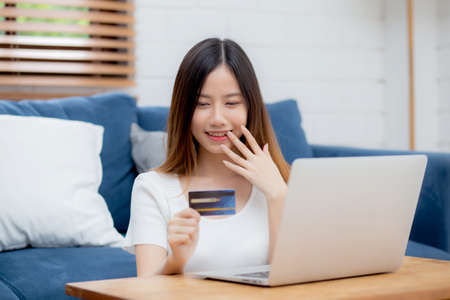 Young asian woman sit on sofa using laptop computer shopping online with credit card buy to internet and surprise, happy girl payment with e-business on couch, success and excited, business concept.