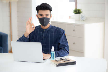 Young business man in face mask working from home with laptop computer on desk for protection for outbreak of covid-19 and healthcare, male quarantine stay home using notebook on desk, new normal. Stok Fotoğraf