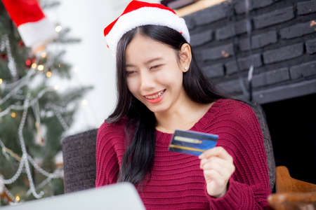 Young asian woman online shopping in Christmas with credit card on laptop computer, female buying and payment with debit card, xmas in holiday, happy new year, customer with purchase to internet.