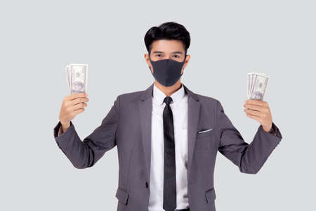 Young asian businessman in face mask holding money dollar isolated on white background, pandemic and crisis of economic, business man in medical mask and investment during disease covid-19. Stok Fotoğraf