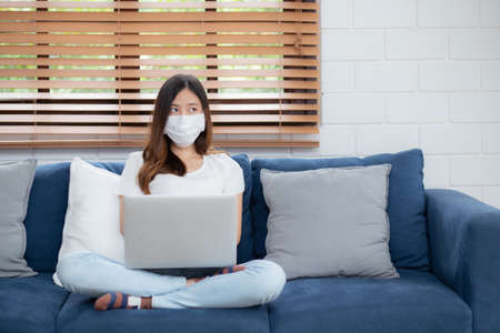 Young asian business woman in face mask think idea and work from home on laptop computer online to internet in living room, girl in medical mask and quarantine for covid-19, stay home, new normal.