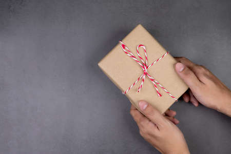 Hand of man holding kraft gift box on cement floor in Christmas day or holiday, present box for anniversary or birthday or celebration with copy space, celebrate and festive, top view, flat lay. Stok Fotoğraf