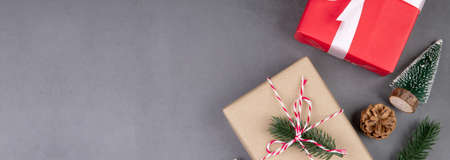 Christmas holiday composition with red gift box decoration on cement floor background, new year and xmas with presents on concrete in season, top view or flat lay, copy space, banner website.