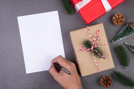 Christmas holiday with gift box decoration and greeting card, new year and xmas or anniversary with presents and hand writing postcard on cement floor background, top view or flat lay, copy space.