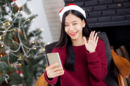 Young asian woman selfie video call online with friends in Christmas day on phone at home with social distancing, new normal, female video conference on smartphone, communication and holiday concept.