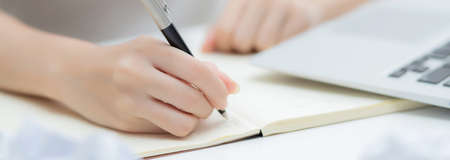 Closeup hand of young asian woman work and writing for planning on notebook on table at home, girl thinking idea and creative, finance and communication, freelance and business concept.