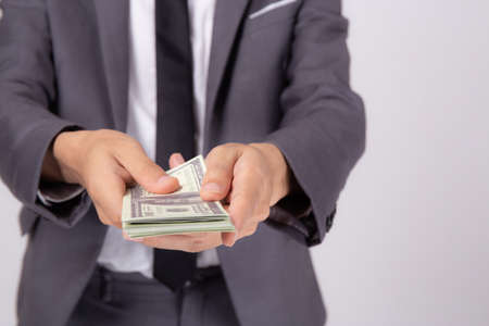 Hand of business man giving money isolated on white background, finance and cash, businessman holding banknotes dollar, deposit and loans, profit bonus and success, currency and exchange. Stok Fotoğraf