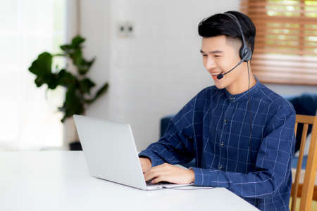 Young asian businessman working on laptop computer wearing headphone at home, business man wearing headset for video conference, communication and education, male study and learning for e-learning.