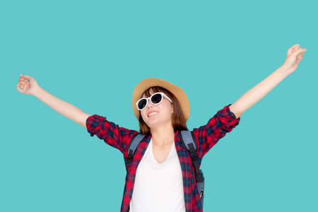 Beautiful portrait young asian woman wear sunglasses and hat smile excited and confident enjoy summer trip holiday isolated blue background, girl cheerful having backpack in vacation, travel concept.