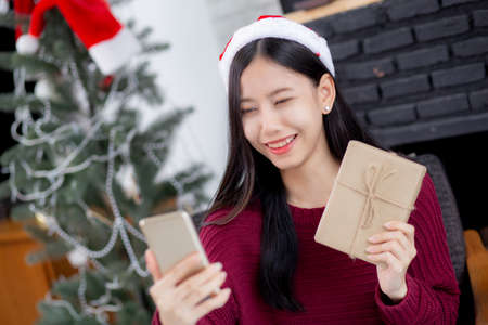 Young asian woman selfie video call online with friends and show gift box in Christmas day on phone at home, social distancing, new normal, female video conference, communication and holiday concept.