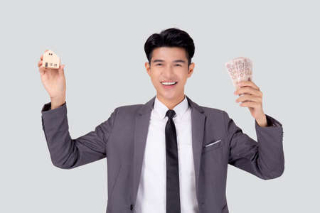 Young asian business man holding home and money Thai for planning saving future, insurance agent and credit, debt and loan of finance, purchase home and refinance, investment about real property. Stok Fotoğraf