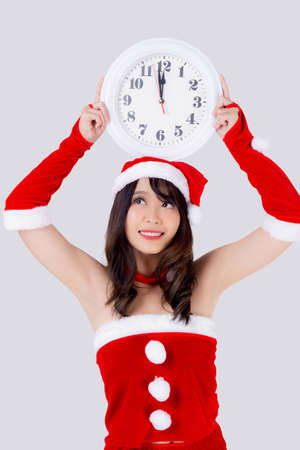 Beautiful portrait young asian woman in Santa dress holding clock with excited in xmas holiday isolated on white background, beauty asia girl celebrating success in festive Christmas day or new year.