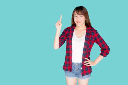 Beautiful portrait young asian woman smiling gesture pointing something and excited summer holiday isolated blue background, asia girl confident and cheerful with journey, travel concept. Stok Fotoğraf